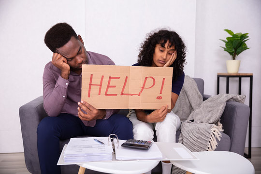 Couple Holding Help Sign While Calculating Bills
