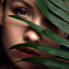 Stores photo Spa Brunette european woman on a neutral dark background with leaves on her face. She have flawless fresh clean skin. Eco spa concept