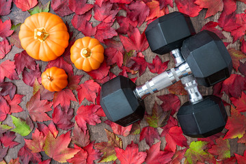 Pair of crossed dumbbells on a rustic wood background covered in fall color of red, green, yellow, and orange maple leaves, with ceramic pumpkins