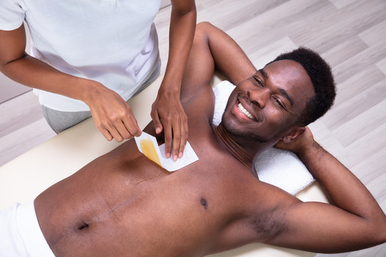 Person Hands Waxing Man's Chest