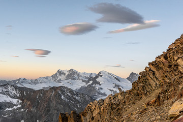 Early morning sunrise view of the Monte Rosa Mountain group and Strahlhorn mountain in the Swiss alps, seen from a steep ridge section on the way up to Weissmies mountain (4017m), Switzerland.