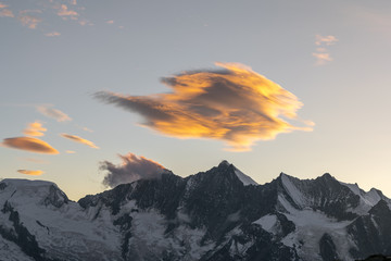 Stunning evening sunset view of the Mischabel Group, part of the Pennine Alps in Switzerland with Alphupel, Taeschhorn, Dom, Lenzspitze & Nadelhorn from left to right. Beautifully illuminated clouds.