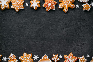 Christmas background with homemade gingerbread cookies on black table, copy space. Festive food, New Year celebration traditions