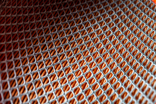 iron mesh frame of paper car air filter, closeup of spare parts with square pattern. background on a car theme.