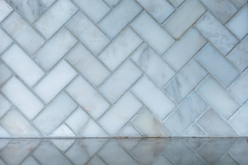white and gray herringbone italian marble tile in a kitchen as a backsplash with the reflection on the granite countertop