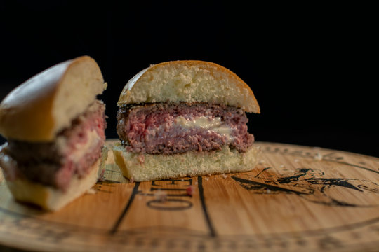 Delicious halved jucy lucy burger stuffed with cheese on a wooden board