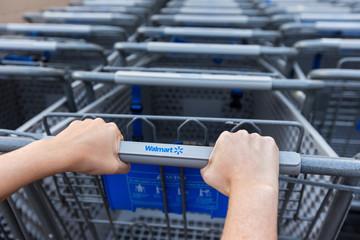 Woman taking shopping cart near Walmart supermarket