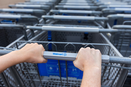 Woman taking shopping cart near Walmart supermarket