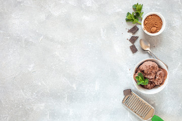 Chocolate ice cream with a bowl on a table. Ice cream, chocolate, cocoa, mint, grater. Summer dessert. Selective focus. Copy space. Flat lay.