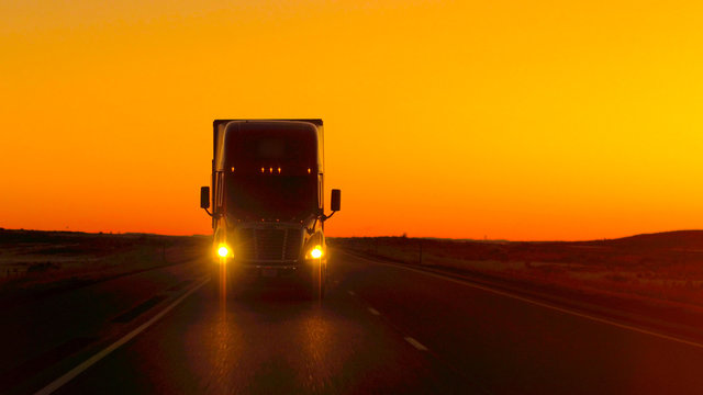 CLOSE UP LENS FLARE: Semi truck driving directly into camera at golden sunset