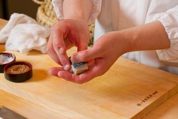 Sushi craftsman holding sushi