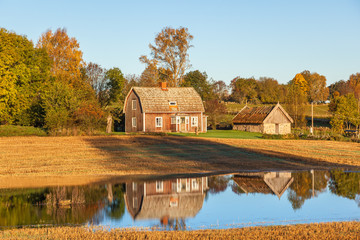Wall Mural - Old abandoned farmhouse with reflections in the water at the field