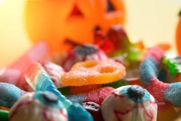 halloween candies with orange pumpkin in the background