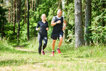 Stores à enrouleur Jogging man and woman jogging and running outdoors in forest