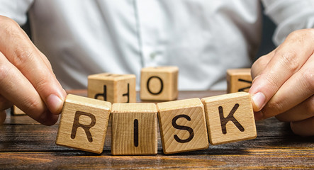 The man carelessly raises the word Risk. High risks in business, fragile balance and insecurity....
