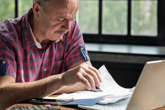 Serious mature hispanic man man checking home finance
