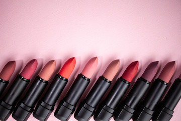 lipstick in different natural colors in a row at the bottom of the picture on a pink background. Top view with selective focus copy space
