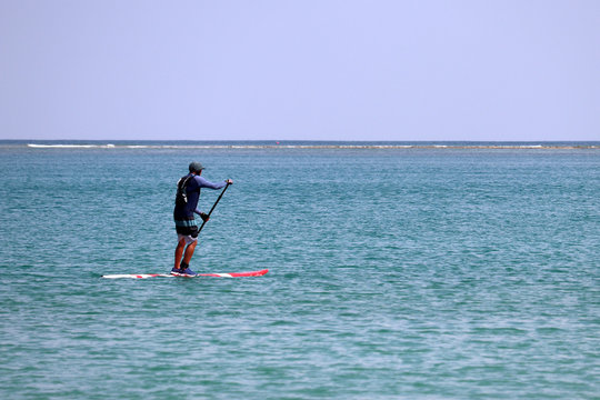 Man with paddle standing on a board in open sea, sup surfing. Surfer on a blue water, standup paddleboarding