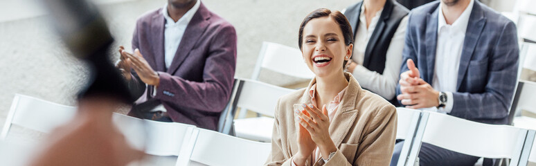 panoramic shot of attractive businesswoman smiling and clapping during conference Fototapete