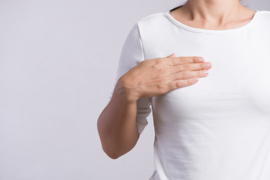 Woman hand checking lumps on her breast for signs of breast cancer on gray background. Healthcare concept.