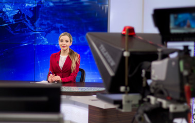 News anchor in the TV Studio . Beautiful girl reading the news, on a blue screen background