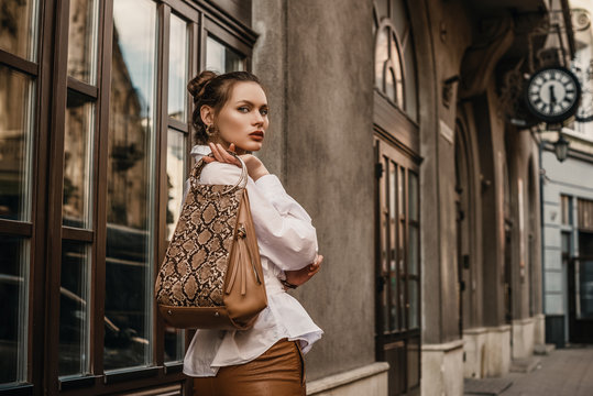 Outdoor fashion portrait of elegant, luxury woman wearing trendy white shirt, holding stylish beige, brown reptile, snakeskin, python print bag, handbag, posing in street. Copy, empty space for text