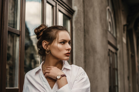 Outdoor fashion portrait of elegant, luxury brunette woman wearing golden circle earrings, brown wrist watch, trendy white shirt, posing in street of European city. Copy, empty space for text