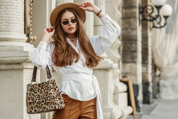 Outdoor fashion portrait of elegant, luxury lady wearing beige hat, black sunglasses, trendy white shirt, brown leather trousers, holding animal, leopard print handbag. Copy, empty space for text  Wall mural