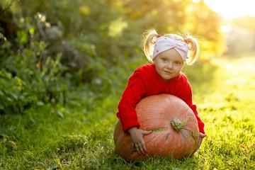 little girl with pumpkin in autumn Park