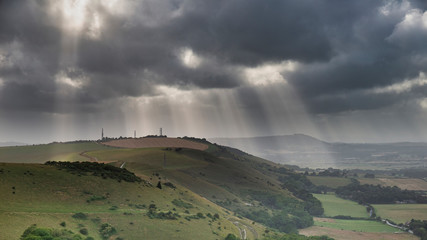 Poster Khaki Stunning Summer landscape image of escarpment with dramatic storm clouds and sun beams streaming down