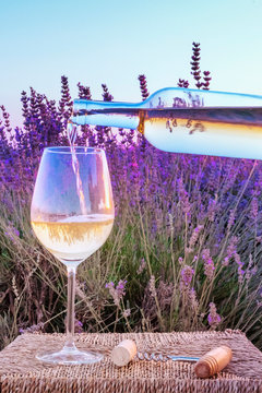 White wine poured into a glass against a lavender field