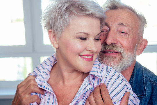 old man hard hugging her young wife with blonde hairstyle and red lipstick