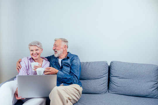 elderly couple in love sitting gray couch in living room look at screen laptop and drinking cup of tea or coffee copyspase