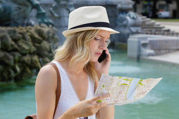 young female tourist looking at map and talking on telephone