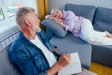 beautiful short haired goog-looking woman lying on the couch,old man artist sitting next to her on chair and drawing in day light living room with big window