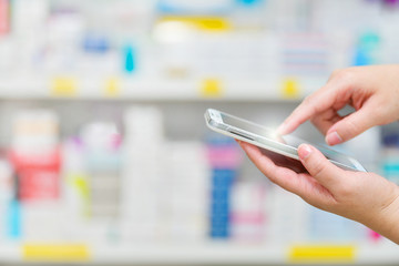 Poster Pharmacie Pharmacist using mobile smart phone for search bar on display in pharmacy drugstore shelves background.Online medical concept.