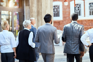 Back of four businessmen walking down the street. Men brunet wear gray jacket and checked jacket. Woman blonde wear black vest, another blonde woman just white shirt