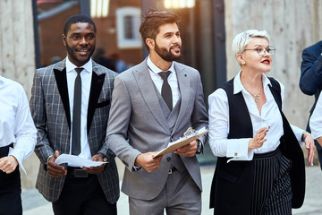 Three businessmen move outdoor. African man in checked jacket and caucasian man in grey jacket keep papier. Blonde caucasian woman move energetically.