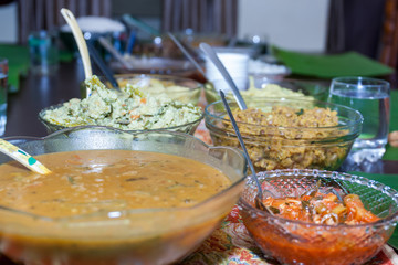 Dining table with Kerala vegetable curries in dishes served during Onam Sadhya on the occasion of Onam festival