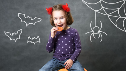 Halloween concept. Little girl with costume horns having fun. Adorable child with bats and spider. Cute toddler smiles and eats Halloween treats of pumpkin cookie. Studio portrait of cheerful kid.