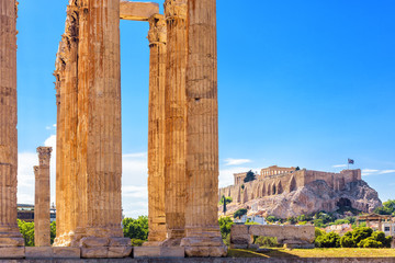Fototapete - Olympian Zeus temple in summer, Athens, Greece. It is one of top landmarks of Athens. Great columns of the famous Zeus house overlooking Acropolis of Athens. View of majestic Ancient Greek ruins.