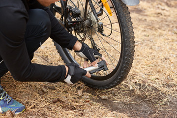 Close up of man hands pumping bicycle wheel, home maintenance of bike, bicycle service and maintaining for new season, faceless picture of wheel with flat tire, male reparing his bike in open air.