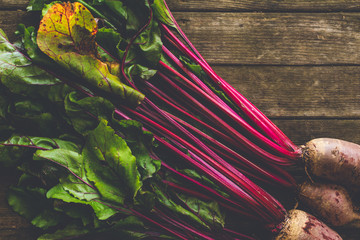 fresh raw beet root vegetables with soil on wooden surface. natural organic food background