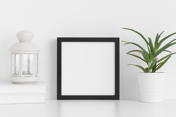 Black square frame mockup with a aloe vera in a pot, candle holder and a book on a white table.