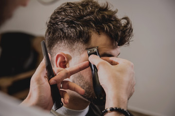 Foto auf Acrylglas Friseur Young man with trendy haircut at barber shop. Barber does the hairstyle and beard trim.
