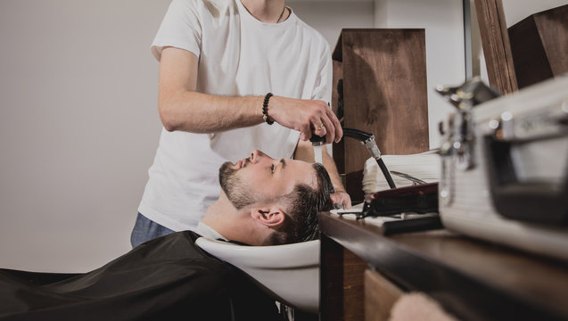 Young man with trendy haircut at barber shop. Barber washes customer head.