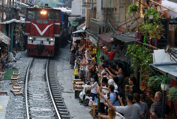 Tourists take photos along a railway as the train passing through an old quarters streets in Hanoi,
