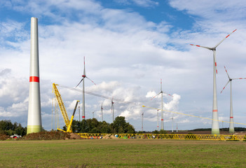 A new wind turbine is erected in a wind farm with the help of a large yellow crane