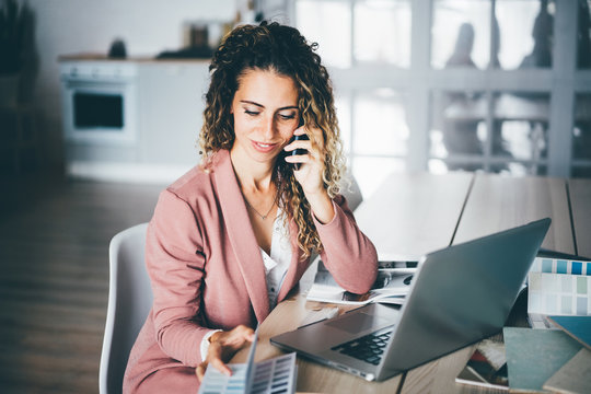 Woman designer drawing sketches of interior. Female designer noting details of work during phone conversation. Young successful woman working from home.