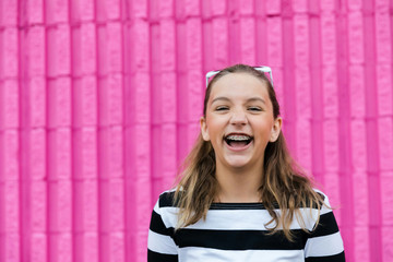 Cute and very happy caucasian girl celebrating her 13th birthday laughing outside in front of a hot pink vibrant color wall laughing
